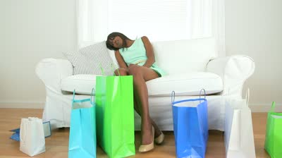 stock-footage-african-american-woman-with-shopping-bags-resting-on-couch